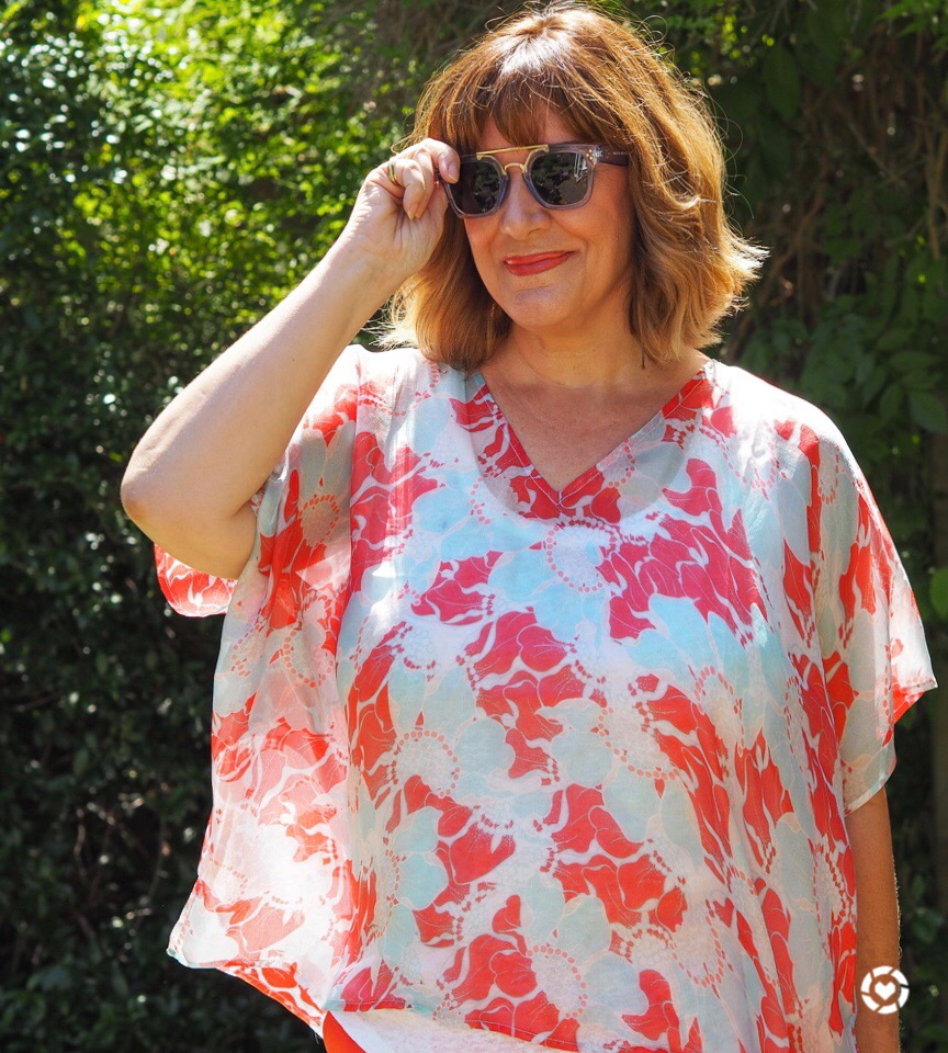 Maria Sadler stylist and fashion blogger wearing coral silk top from Pure Collection and blue sunglasses