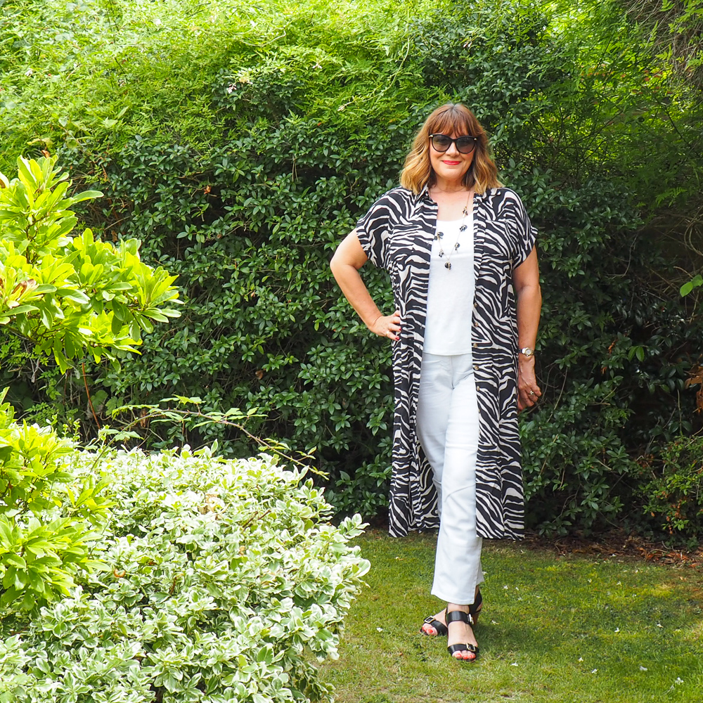 maria sadler, stylist, fashion blogger wearing zebra print shirt dress, white jeans, white vest top