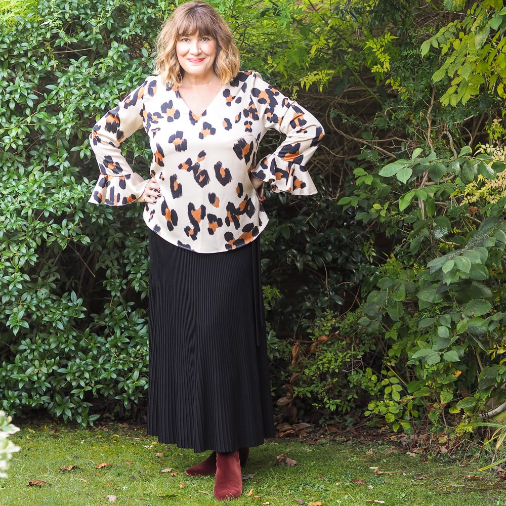 High/Low styling trick, Maria Sadler stylist wearing Weekend Maxmara black pleated skirt with animal print blouse, velvet boots