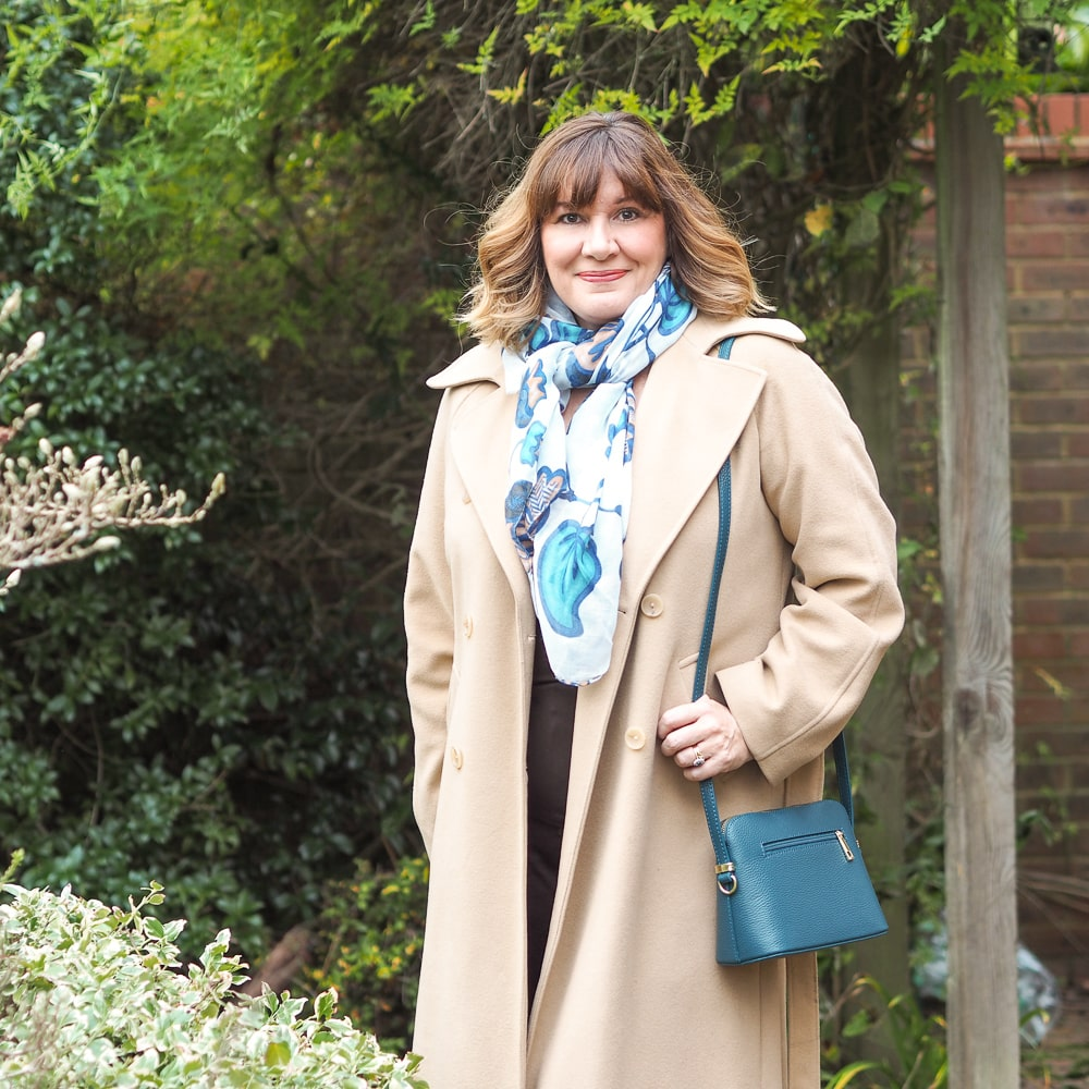 the coats you need in your winter wardrobe, Maria sale stylist wearing camel coat, capsule accessories teal bag, print scarf