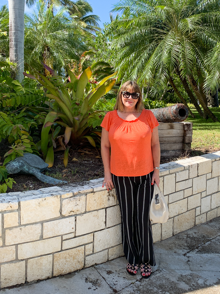 beach holiday capsule wardrobe, Maria Sadler, stylist and fashion blogger wearing stripe beach trousers and orange top at Curtain Bluff Antigua