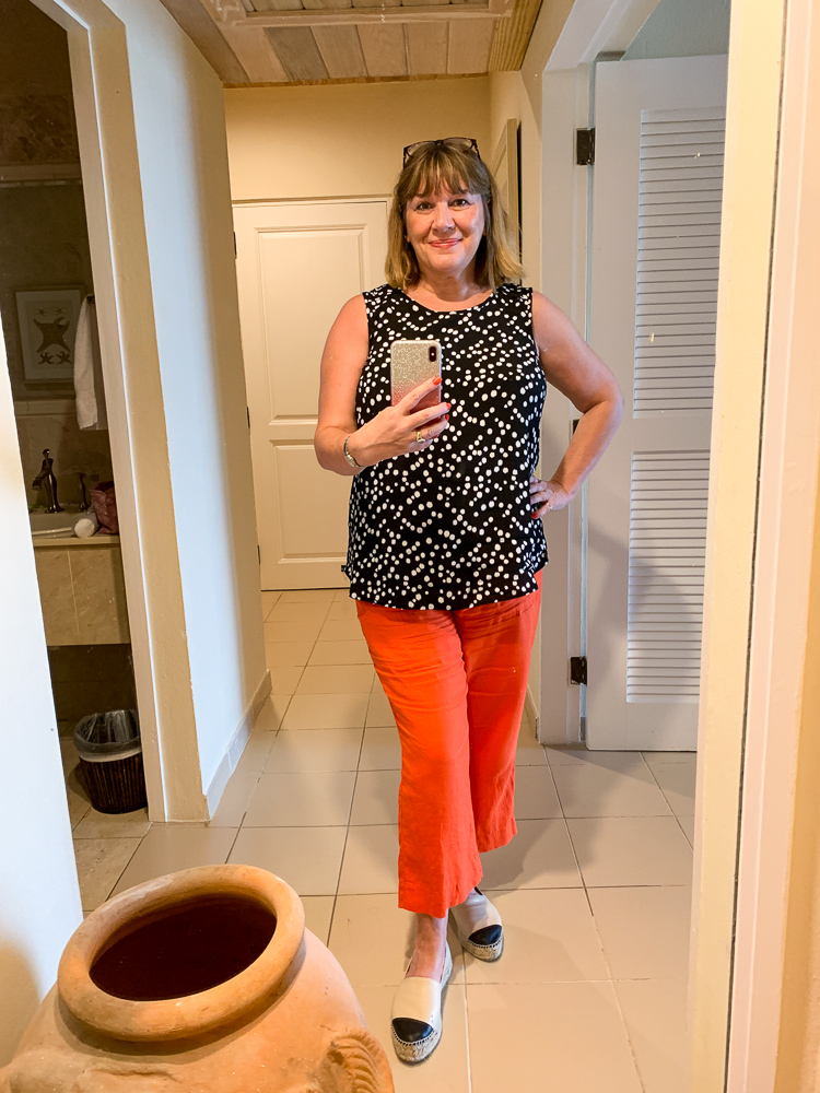 beach holiday capsule wardrobe, Maria Sadler, stylist and fashion blogger wearing orange linen trousers and black white spot top at Curtain Bluff Antigua