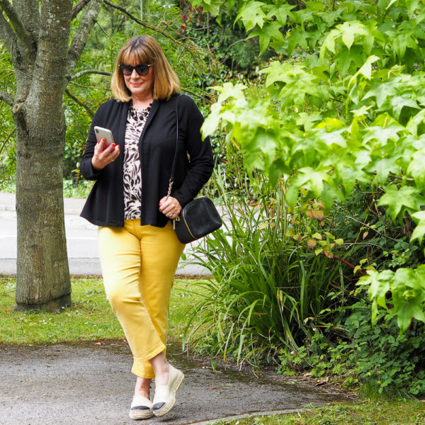 best jeans for women over 40, yellow cropped jeans, black blazer animal print top