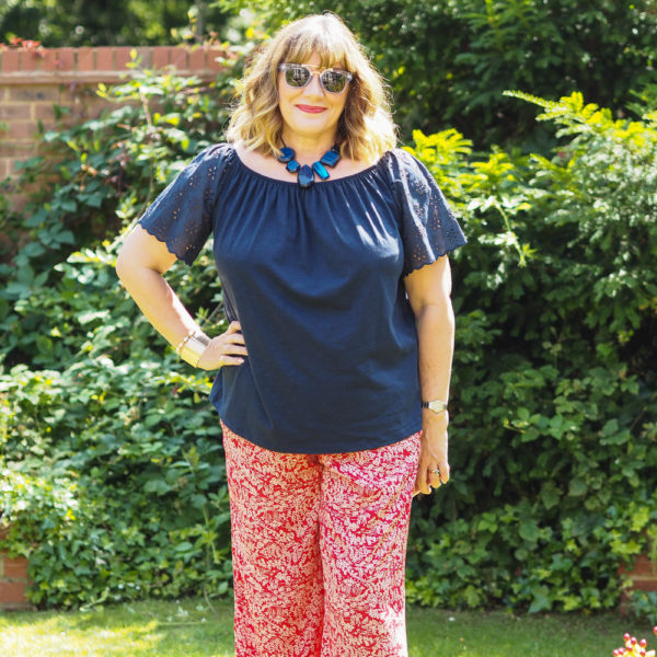 How to wear wide leg trousers, red print trousers with navy bardot top blue sunglasses